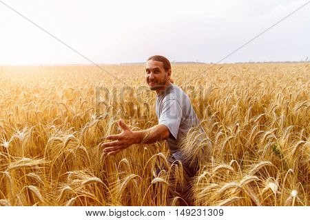 Funny man in field of wheat reaches out to the audience in the sunset light.