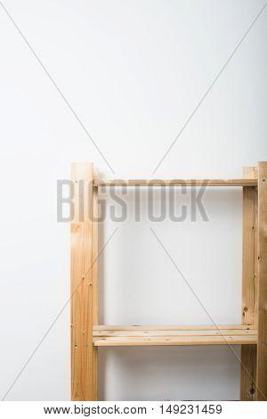 Empty wooden shelf by th wall, minimalist scandinavian furniture on white background