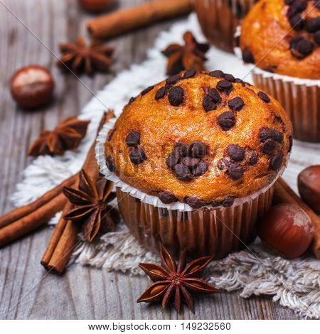 Food and drink, seasonal concept. Homemade chocolate chip muffins with nuts and anise stars, cinnamon for breakfast on a rustic wooden table. Selective focus