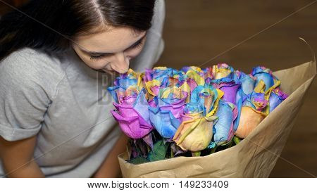 young woman is smelling bouquet of rainbow roses.