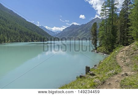 The trail runs along the shore of the Kucherla lake. Altai Mountains Russia. Sunny summer day.