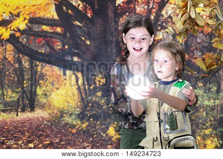 Two young explorers amazed at the ball of light they've found in the autumn woods.