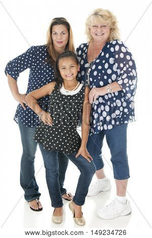 Three generations of women happily standing together in their navy and white polka dot tops.  On a white background.