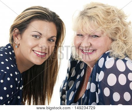 A young woman with her mature mother facing each other in their polka dot dresses.  On a white background.