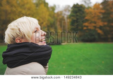 Portrait of smiling cute blonde on a background autumn forest closeup in profile