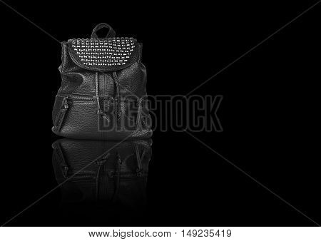 luxury leather black bag with diamond studs and dual zipper for women on black background and reflection shadow isolated included clipping path