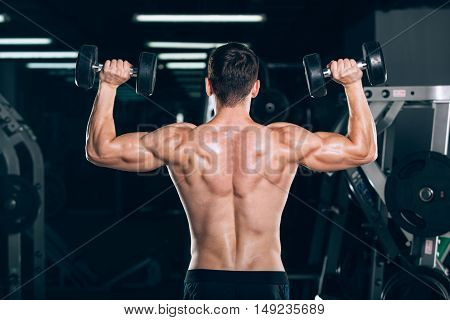 sport, fitness, lifestyle and people concept - Muscular bodybuilder guy doing exercises with dumbbells in gym