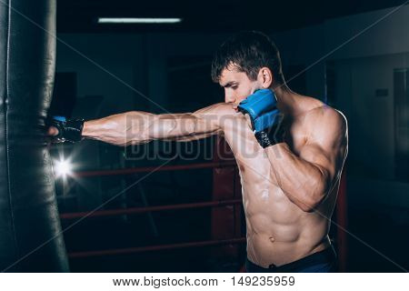 Young Male boxer using a punching bag in gym. Boxer hitting punching speed bag in gym, head and shoulders. Athlete with blyu boxing gloves.