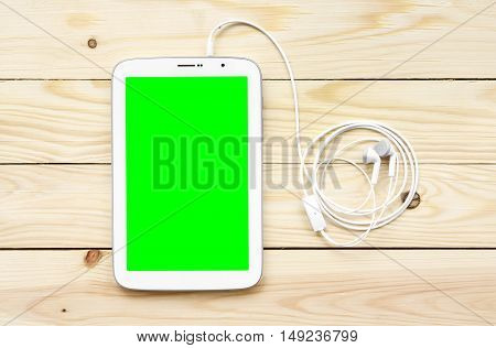 white tablet green screen display with earbuds on top view wood table included clipping path for tablet display