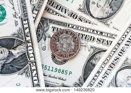 Coin Three Cuban Pesos Over Several Dollar Bills