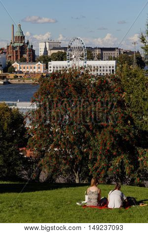 HELSINKI, FINLAND - AUGUST 20, 2016: People resting on the Observatory Hill. It is  one of the best views of the city