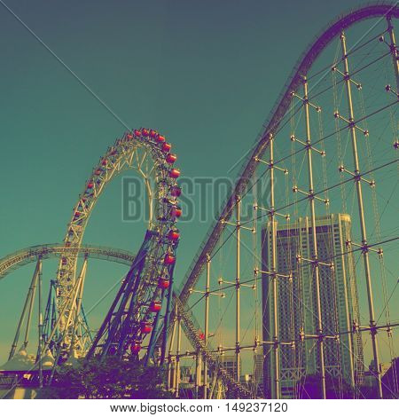 Tokyo - May 2016: Ferris wheel and rollercoaster at Tokyo Dome amusement park. Retro look
