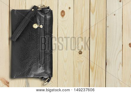 luxury leather black bag or wallet on top view wood table business and fashion trend