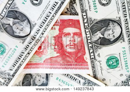 Three Cuban Pesos Bill Mixing Between Dollar Bills