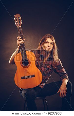 Hobby passion concept. Guitarist is posing with guitar. Long haired performer and his instrument.