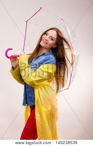 Woman rainy smiling girl wearing waterproof yellow coat standing under umbrella having fun. Meteorology forecasting and weather season concept