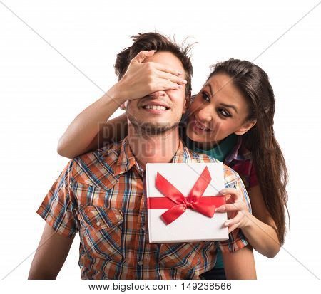 Girl covers eyes boy while gives to him a gift box