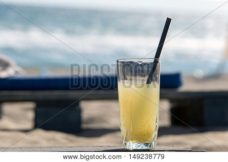 Cup homemade lemonade on the background of the beach on a wooden pallet