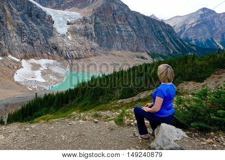 Woman sitting on a stone above glacier lake. Alberta. Canada.