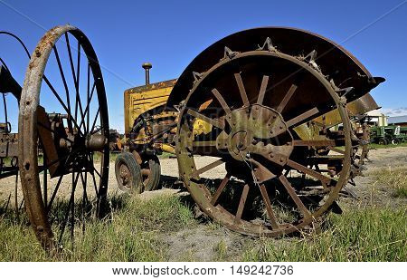 An old yellow tractor in a junkyard with steel wheels and lugs for greater traction.
