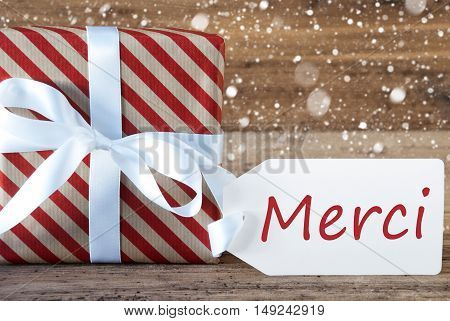Christmas Gift Or Present On Wooden Background With Snowflakes. Card For Seasons Greetings. White Ribbon With Bow. French Text Merci Means Thank You