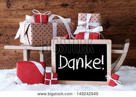 Chalkboard With German Text Danke Means Thank You. Sled With Christmas And Winter Decoration. Gifts And Presents On Snow With Wooden Background.