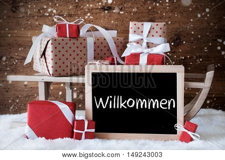 Chalkboard With German Text Willkommen Means Welcome. Sled With Christmas And Winter Decoration And Snowflakes. Gifts And Presents On Snow With Wooden Background.
