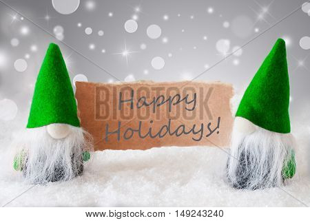 Christmas Greeting Card With Two Green Gnomes. Sparkling Bokeh And Noble Silver Background With Snow. English Text Happy Holidays