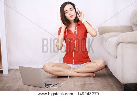 Smiling young woman in headphones sitting on floor at home using laptop and listening music, technology and communication concept