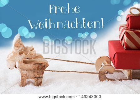 Moose Is Drawing A Sled With Red Gifts Or Presents In Snow. Christmas Card For Seasons Greetings. Light Blue Background With Bokeh Effect. German Text Frohe Weihnachten Means Merry Christmas