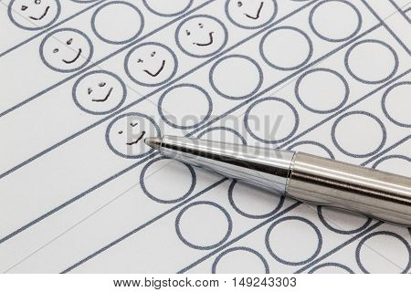 Performance evaluation sheet with a silver pen and hand drawn smileys in circles