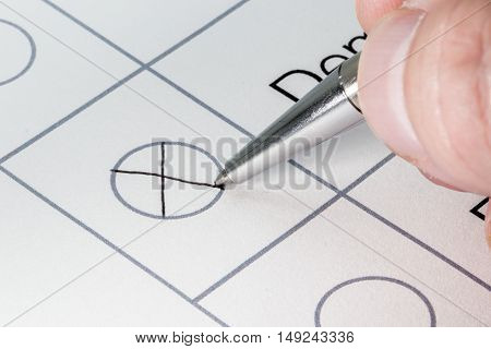 Hand crossing a circle on a paper with a silver pen election poll survey concept