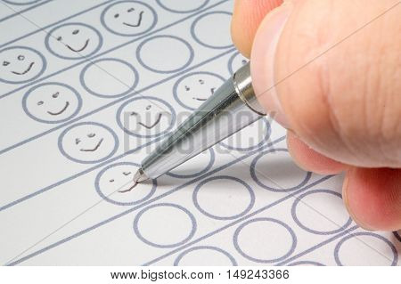 Hand filling out a performance evaluation sheet with a silver pen drawing smileys in circles