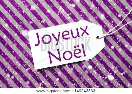 One Label On A Purple Striped Wrapping Paper. Textured Background With Snowflakes. Tag With Ribbon. French Text Joyeux Noel Means Merry Christmas