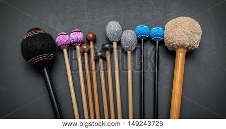 nice, amazing detailed closeup view of various drum and percussion orchestra natural hickory wood sticks on dark grey background