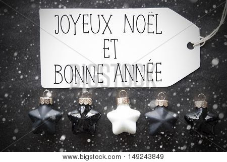 Label With French Text Joyeux Noel Et Bonne Annee Means Merry Christmas And Happy New Year. Black And White Christmas Tree Balls On Black Paper Background With Snowflakes. Flat Lay View