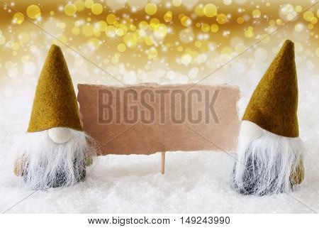 Christmas Greeting Card With Two Golden Gnomes. Sparkling Bokeh And Noble Background With Snow. Copy Space For Advertisement