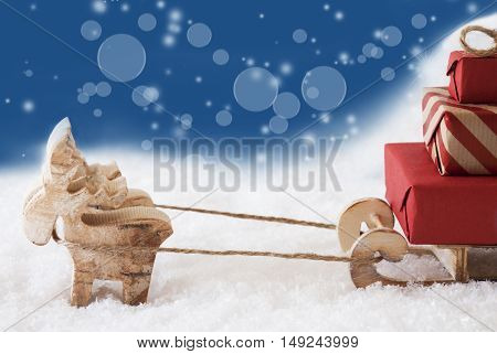 Moose Is Drawing A Sled With Red Gifts Or Presents In Snow. Christmas Card For Seasons Greetings. Copy Space For Advertisement. Blue Background With Bokeh Effect.