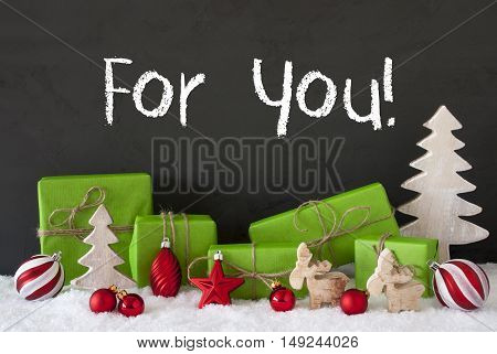 English Text For You. Green Gifts Or Presents With Christmas Decoration Like Tree, Moose Or Red Christmas Tree Ball. Black Cement Wall As Background With Snow.