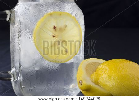 horizontal image of a jar of cold water with ice cubes and a slice of lemon with a full lemon lying beside the glass on black background with room for text.