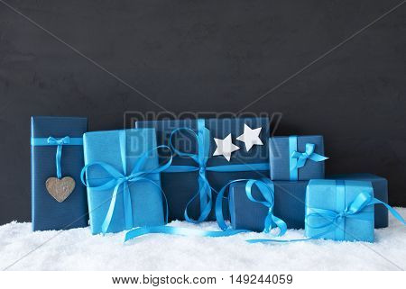 Blue Gifts Or Presents With Hearts And Stars. Black Cement Wall As Background With Snow. Christmas Greeting Card For Seasons Greetings