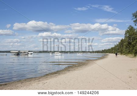 horizontal image of a fleet of boats and ships floating in the lake next to a sandy beach under a beautiful blue sky with cloud on a warm summer day.