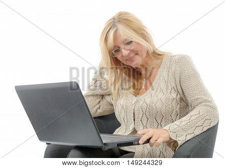 a portrait of a smiling mature woman using laptop