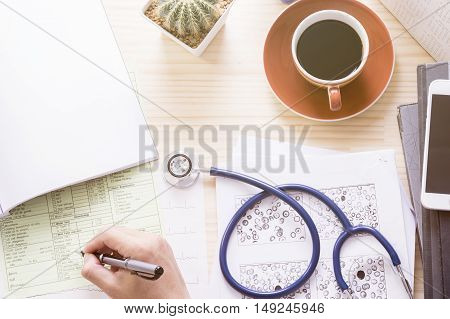 Top view doctor office with cup of coffee, stethoscope, ekg paper, blood test exam and blank document