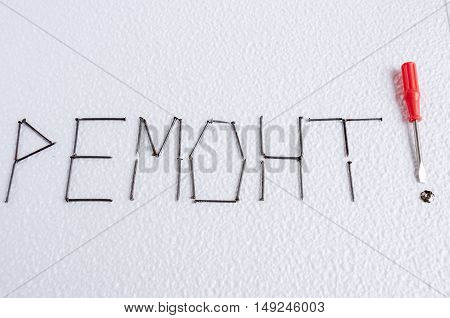 On a white background lined with nails word repair