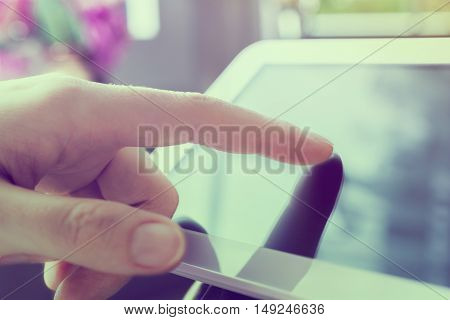 Woman Using Blank Business Tablet In Landscape View Next To A Window