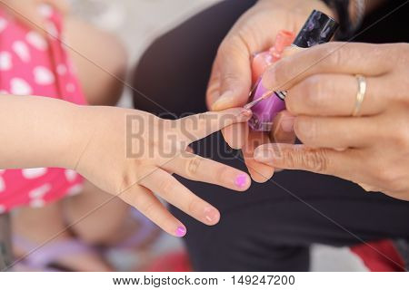 Woman applying nail polish doing manicure to a little girl fun activity at home or girl birthday party