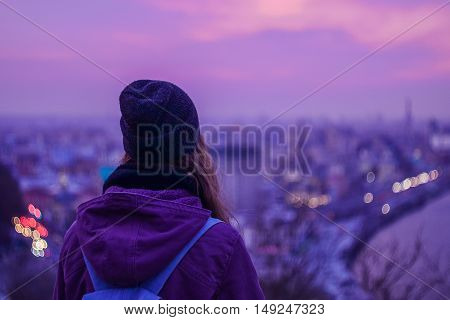 Girl looking at winter evening cityscape purple violet sky and blurred city lights