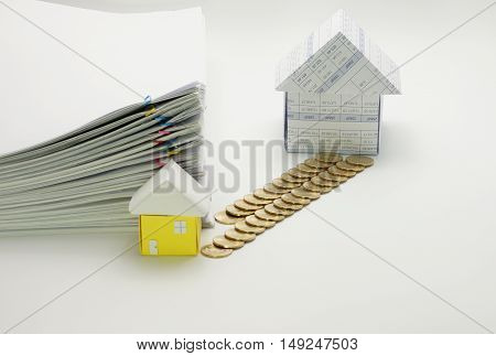 House and pile of gold coins with little house and pile overload paperwork of report with colorful paperclip have blur on white background.