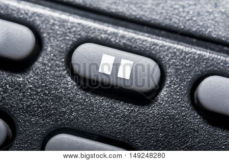 Macro Of A Black Pause Button On Black Remote Control For A Hifi Stereo Audio System